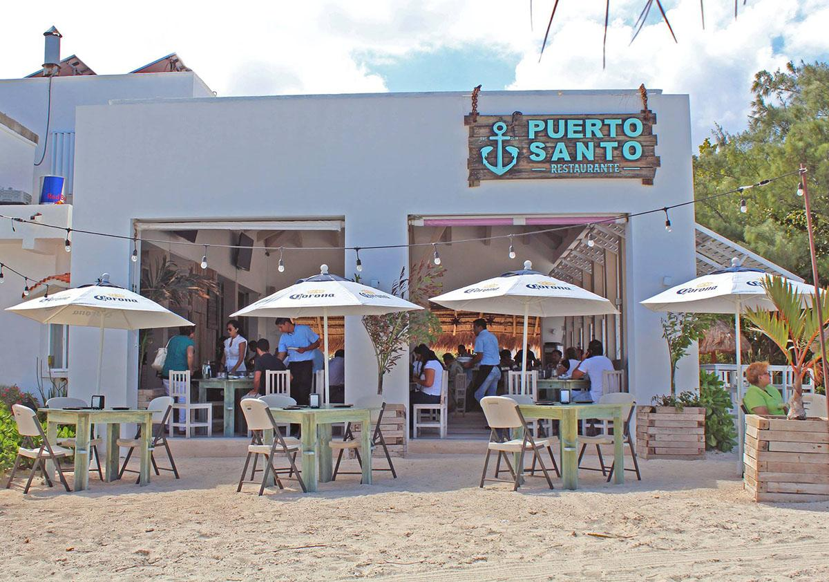 front of a restaurant on the beach with chairs and table and people eating