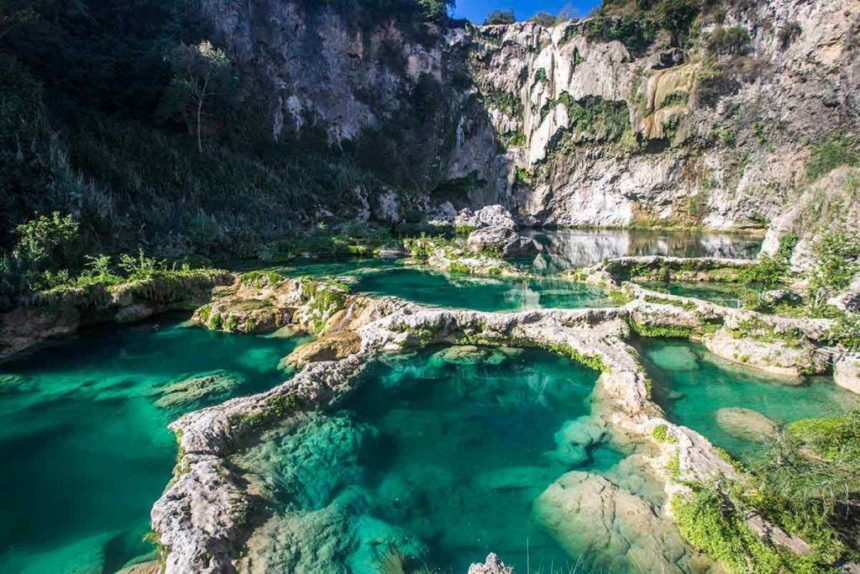 emerald green ponds by a dry waterfall