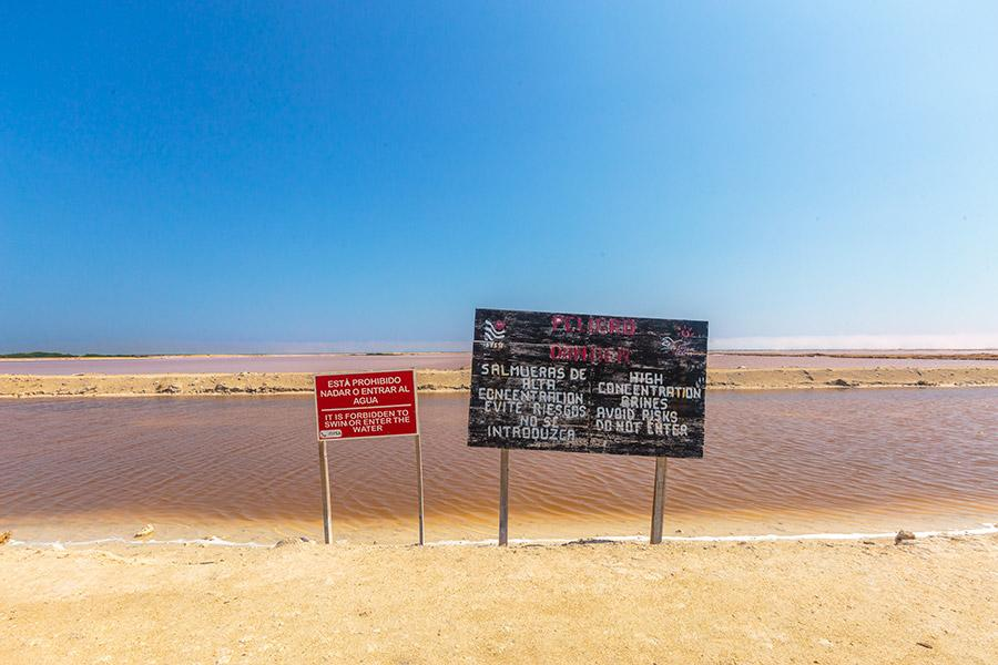 pink lakes and board with warnings
