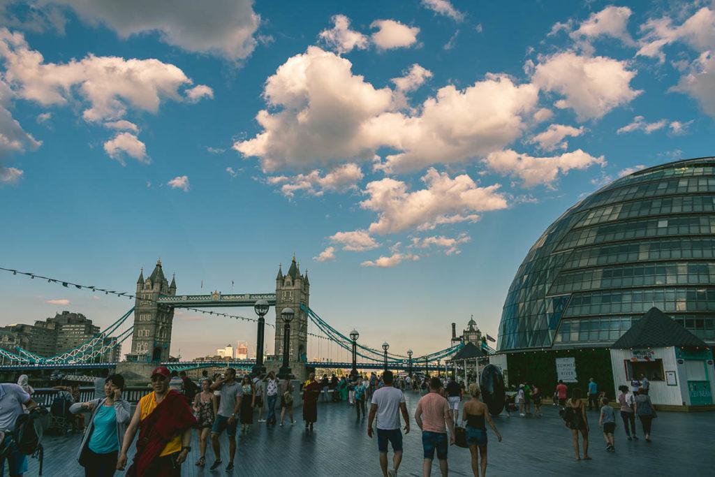 tower bridge, cloudy sky and people walking on the street