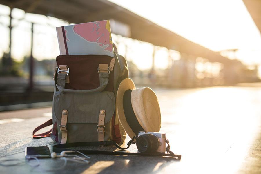 backpack, a hat a camera gear at a station at sunset
