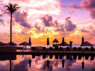 pinky sky at sunset reflecting on a pool lined with palms and umbrellas in a luxury hotel in cancun