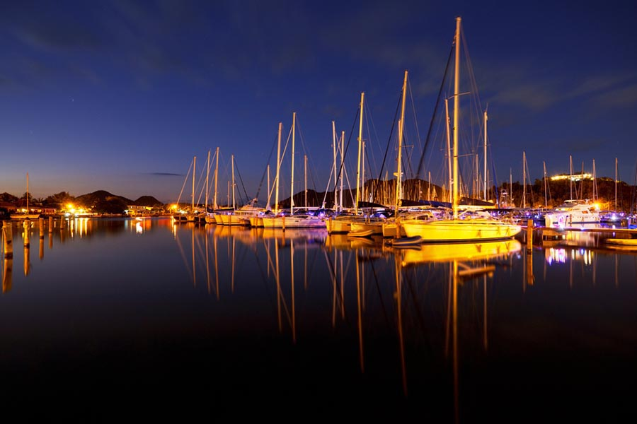 NIght view of a harbor with boats and blue sky