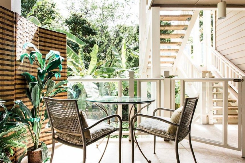 chairs and table on a balcony in front of a lush garden
