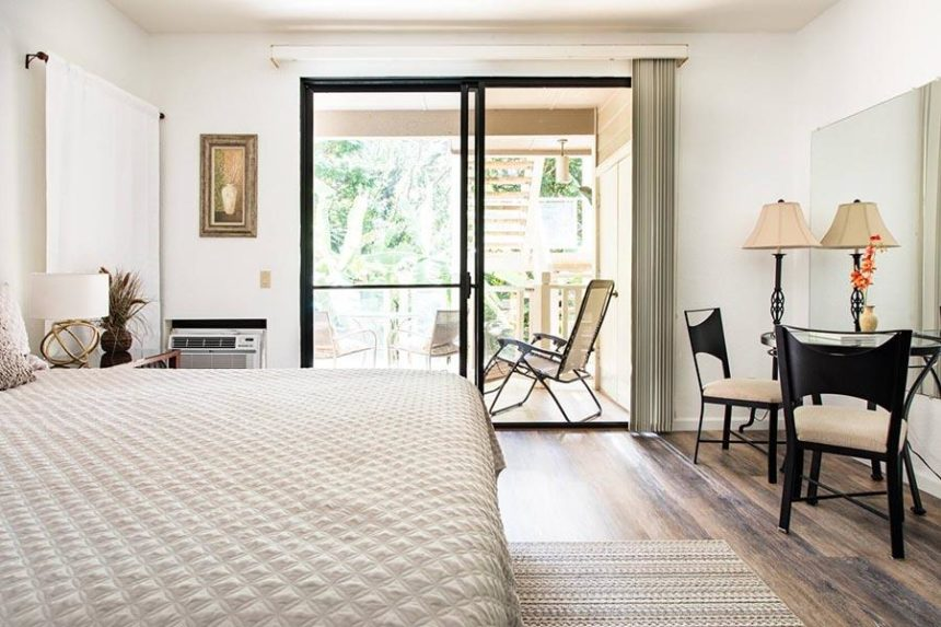 Bedroom with window to a balcony with chairs