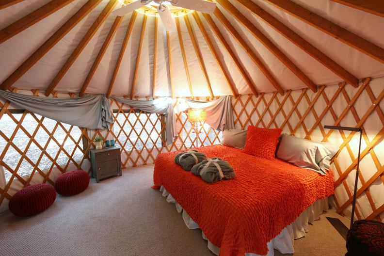 internal of a yurt with a king size bed covered in a red blanket
