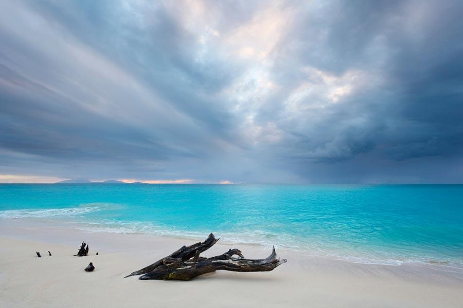 Deserted beach with white sand blue water and cloudy sky