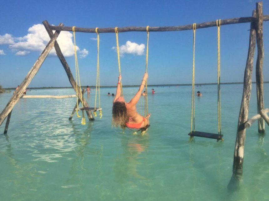 Girl on a swing in a blue lake