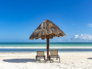 beach chairs with umbrella on a deserted beach in front of a turquoise sea