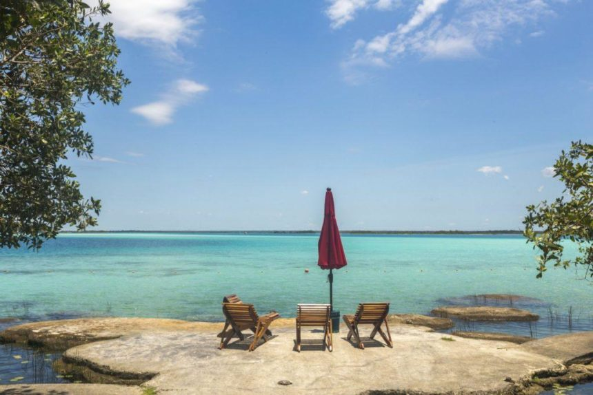 turquoise water lake with trees on the side and a red umbrella with 4 sunbeds on a rocky platform