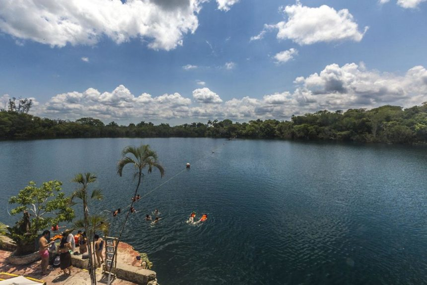 Blue lake with a platform and palm trees around