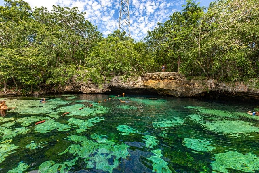 emerald green lake crossed by a cord to hold on to and surrounded by vegetation in the back-ground