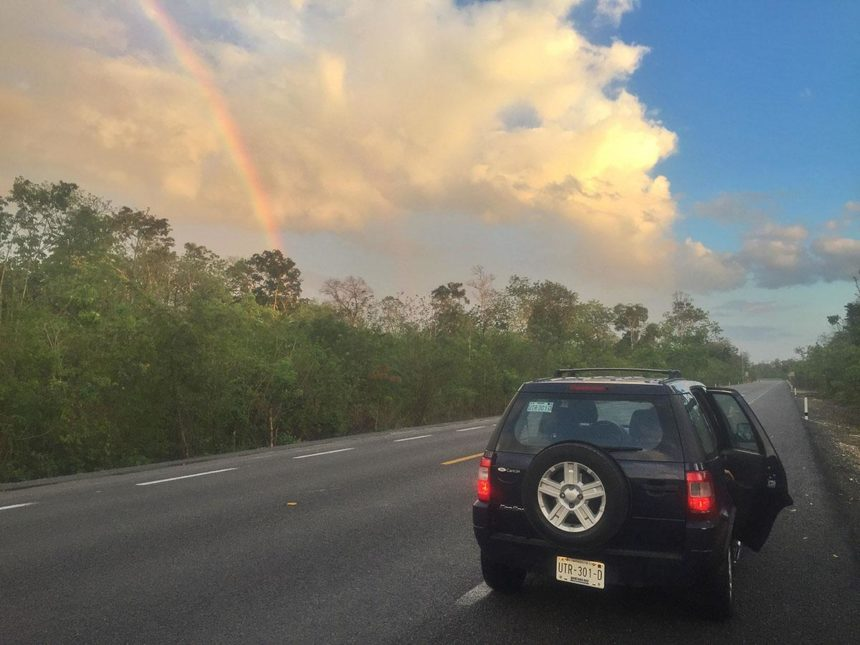 car on the road cloudy sky with a rainbow and jungle on the side