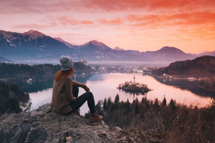 a girl sitting on a montain peak overlooking the amazing lake