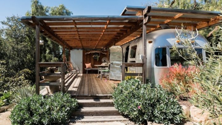 Airbnb Glamping in California - RV in a garden with a porch