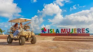 Isla Mujeres letters and a couple on a golf cart