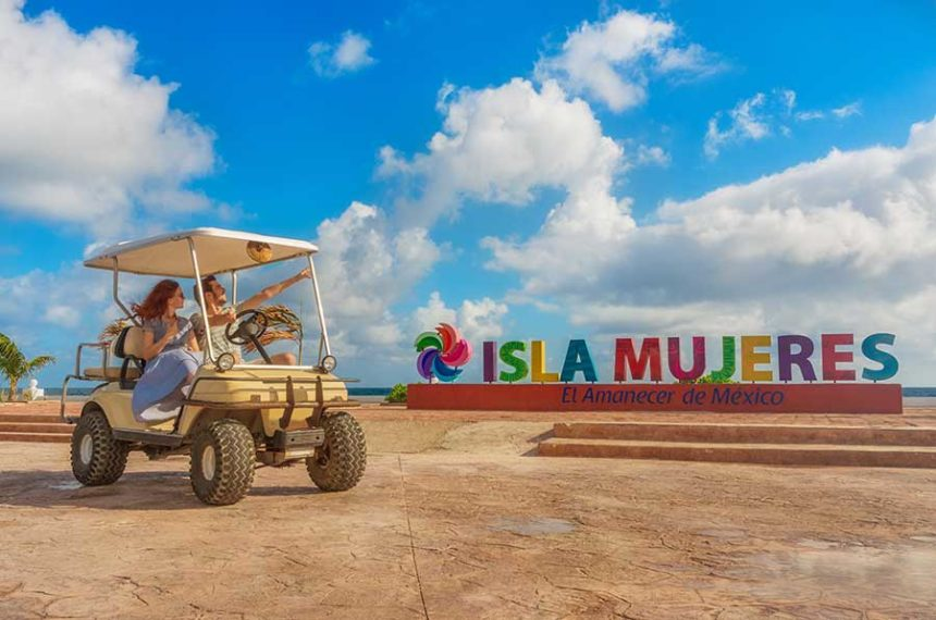 Isla Mujeres letters and a couple on a golf cart - Isla Mujeres Golf Cart Rental