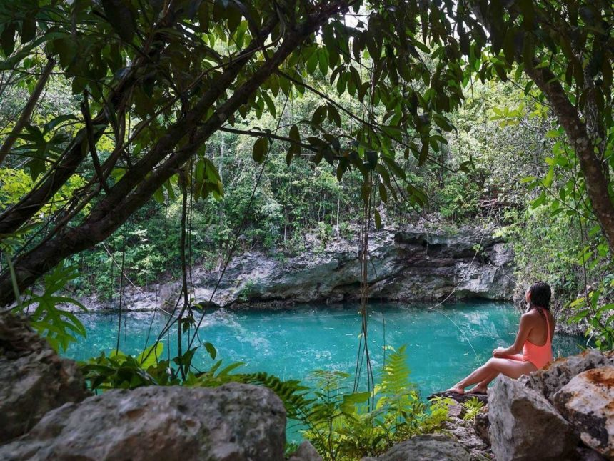 girl looking at a lake surrounded by a tropical jungle