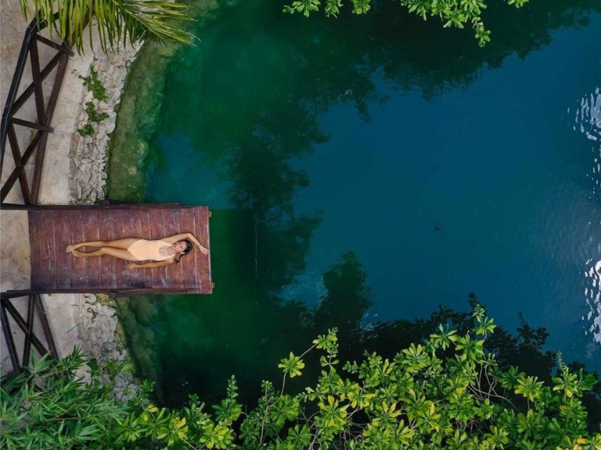 woman laying on a platform over a cenote