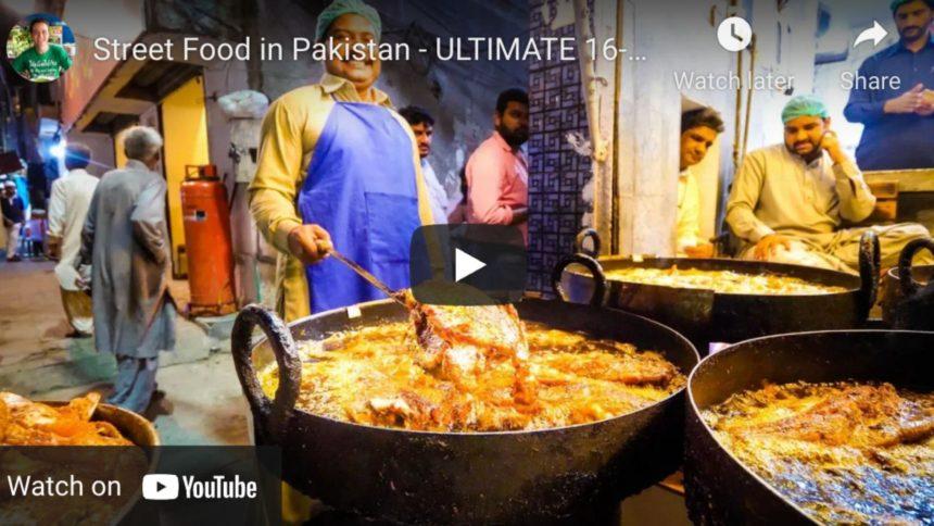 a men stiring a huge pot of food