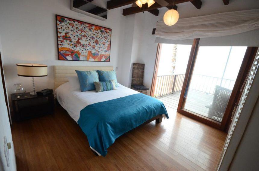 waterfront villa bedroom with blue bedspread