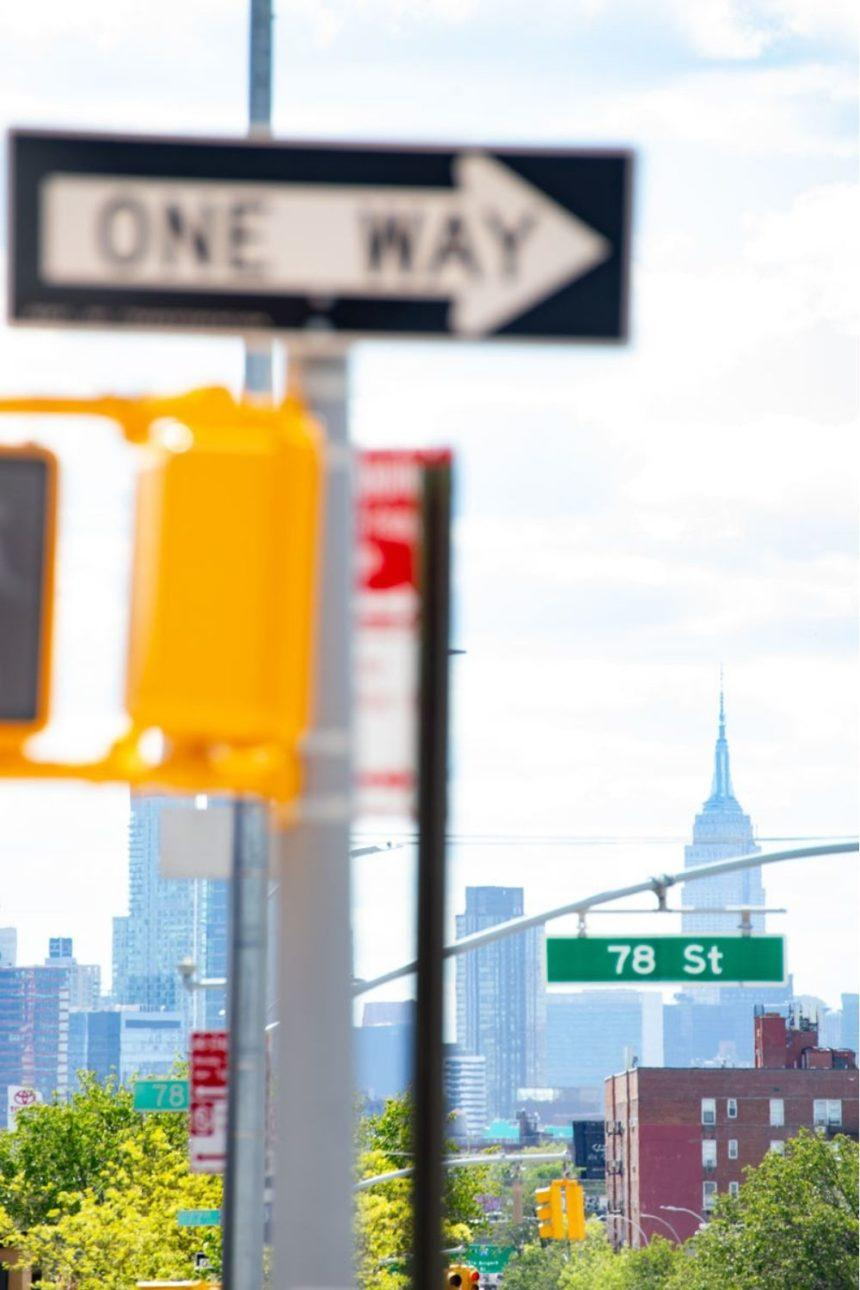 street sign with empire state building in the background