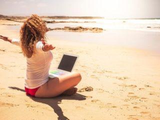 a girl at the computer on a beach