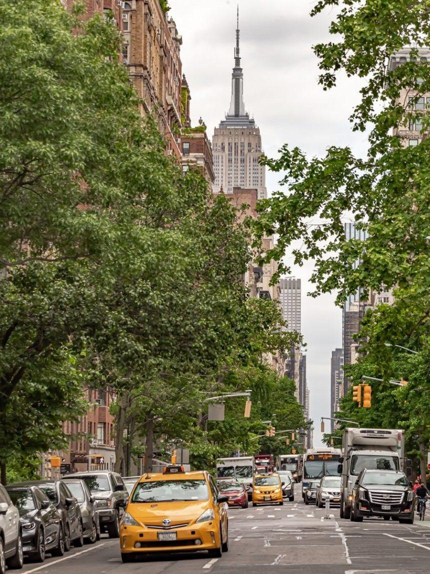 taxi in a road with the empire state building in the back