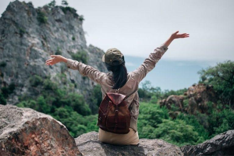 girl opening her arms to the sky on a mountain top