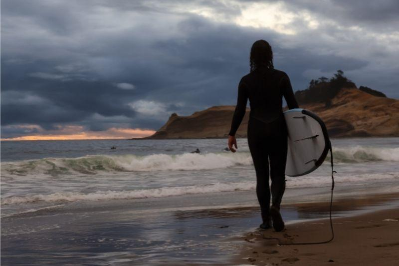girl on a beach with a surfboard under her arm