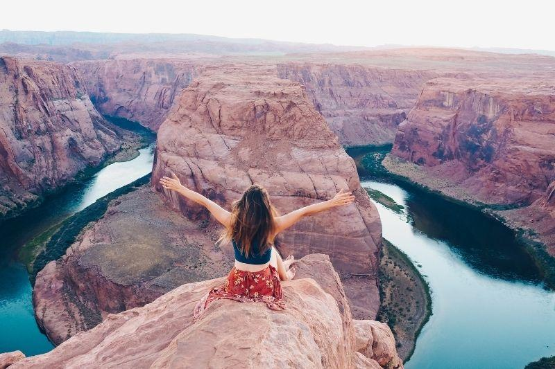 woman sitting on a cliff looking at the landscape