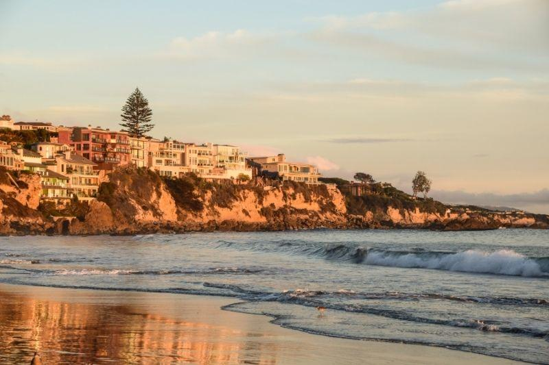 Corona del Mar beach at sunset with homes on the cliff