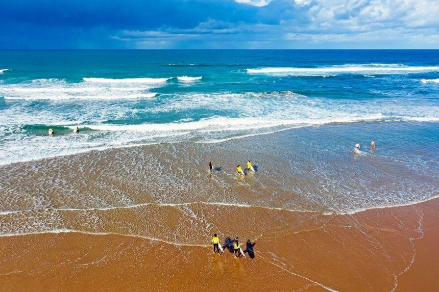 SURFERS ON A BEACH IN PORTUGAL